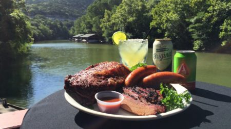 A plate of ribs and other barbeque food with a river in the background.