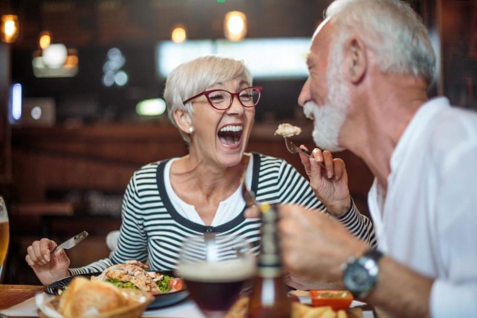 An elderly couple enjoying a meal in an upscale restaraunt
