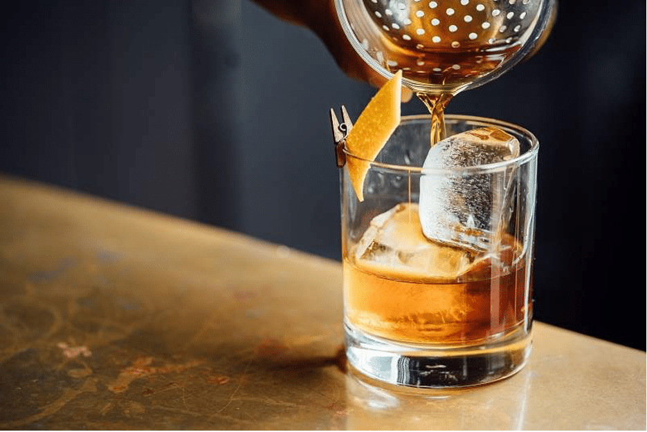 A glass of whiskey strained over ice in a tumbler.