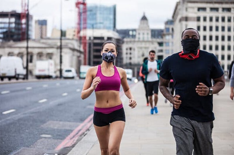 Woman and man jogging with masks on during COVID-19