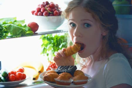 A woman eating food from the fridge at night, an indicator that she needs to change her relationship with food.